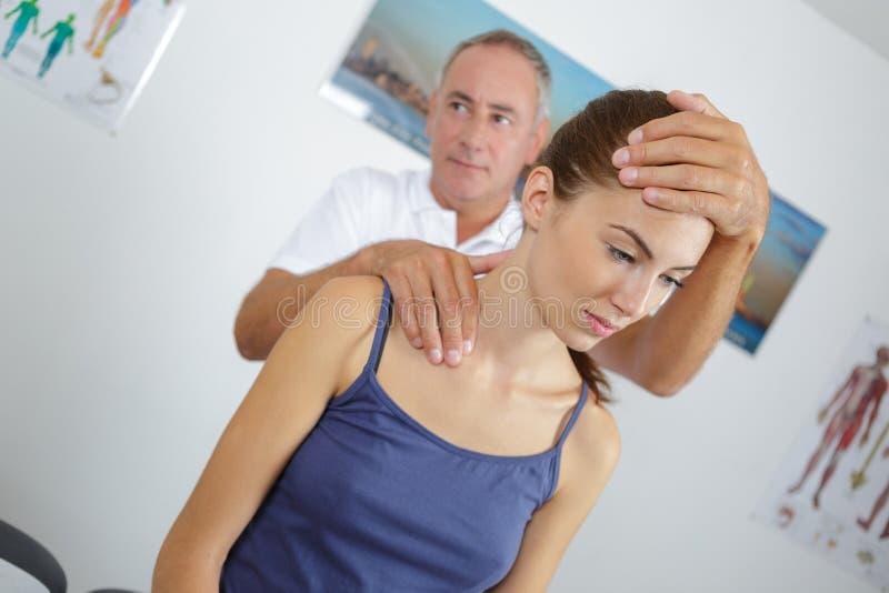 Fysioterapeut som ger halsmassage till kvinnan i klinik arkivfoton