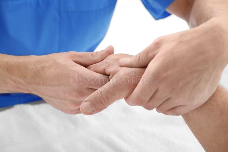 Fysioterapeut som ger handmassage till den höga patienten royaltyfri fotografi