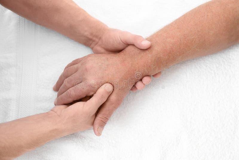 Fysioterapeut som ger handmassage till den höga patienten, royaltyfri foto