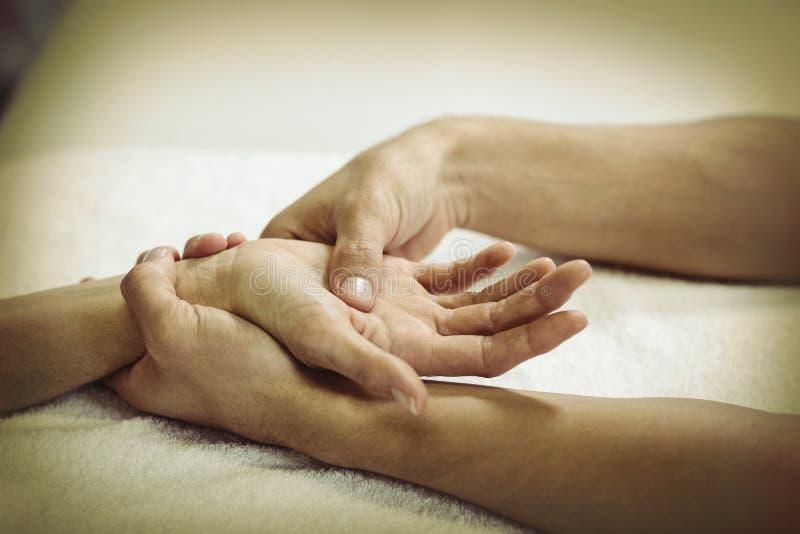 Fysioterapeut som ger handmassage till en kvinna arkivfoton