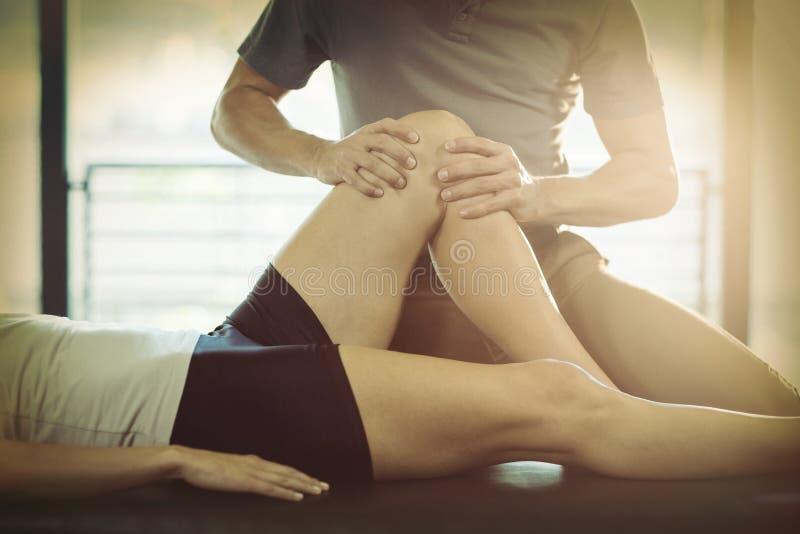 Fysioterapeut som ger knäterapi till en kvinna royaltyfria bilder