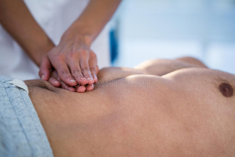 Fysioterapeut som ger magemassage till en man royaltyfri fotografi