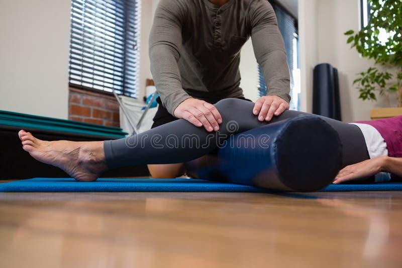 Fysioterapeut som ger sjukgymnastik av benet till patienten arkivbilder