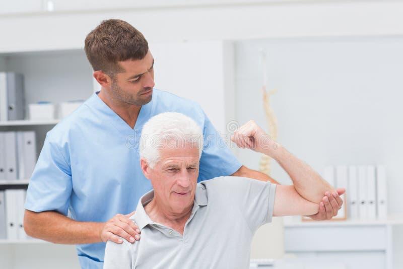 Fysioterapeut som ger sjukgymnastik till mannen arkivfoto