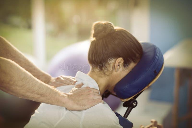 Fysioterapeut som ger skuldramassage till en kvinnlig patient arkivbilder