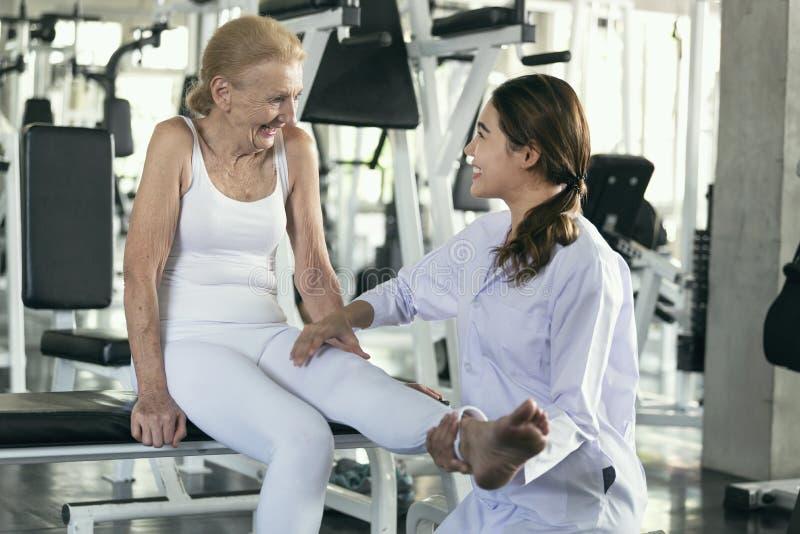 Fysioterapeut som hjälper den gamla höga kvinnan i fysisk mitt äldre vård- livsstilbegrepp royaltyfri foto