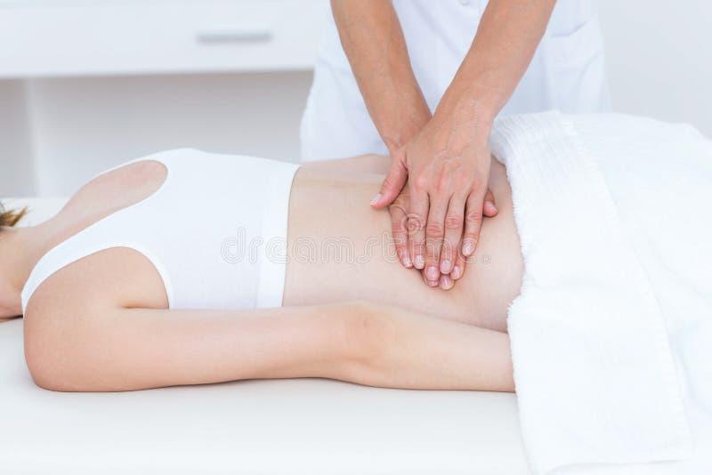 Fysioterapeut som tillbaka gör massage arkivbilder