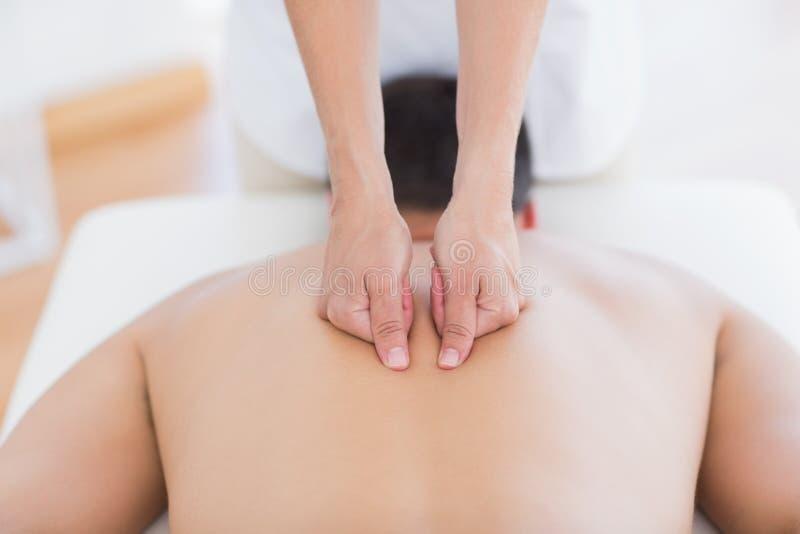 Fysioterapeut som tillbaka gör massage till hennes patient arkivbild