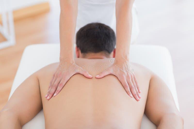 Fysioterapeut som tillbaka gör massage till hennes patient arkivfoto