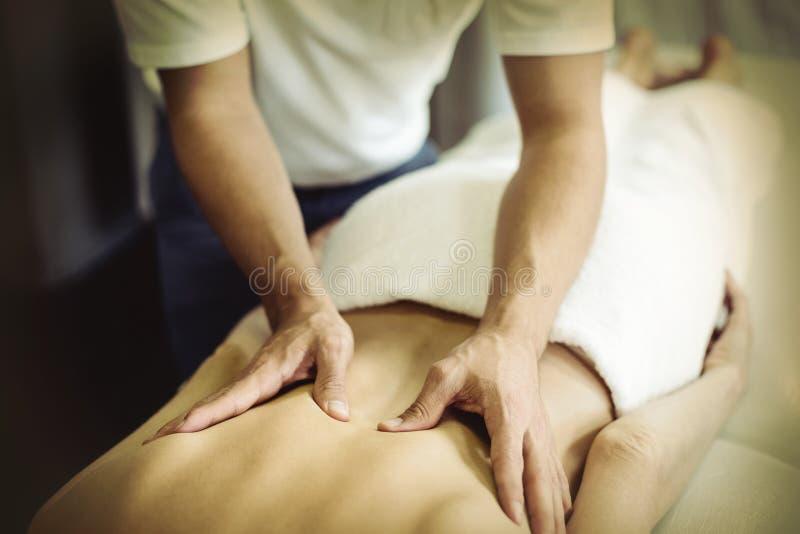 Fysioterapeut som tillbaka ger massage till en kvinna arkivfoton