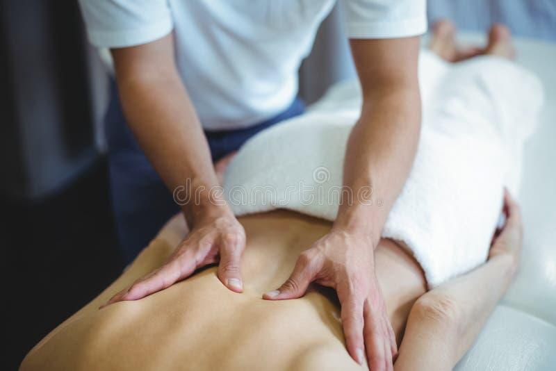 Fysioterapeut som tillbaka ger massage till en kvinna fotografering för bildbyråer