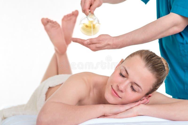 Fysioterapeut som tillbaka ger massage till en kvinna arkivbild