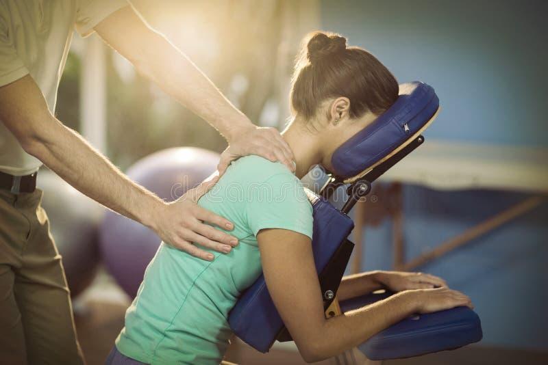 Fysioterapeut som tillbaka ger massage till en kvinnlig patient arkivfoto