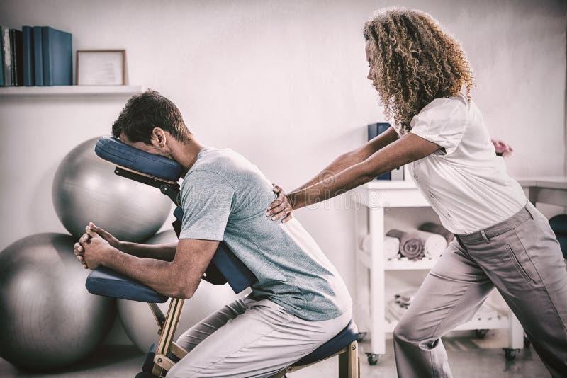 Fysioterapeut som tillbaka ger massage till en patient fotografering för bildbyråer