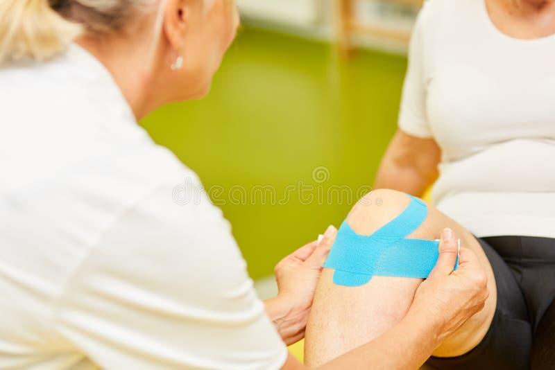 Fysioterapeuten fäster ett kinesioband till knäet arkivfoton