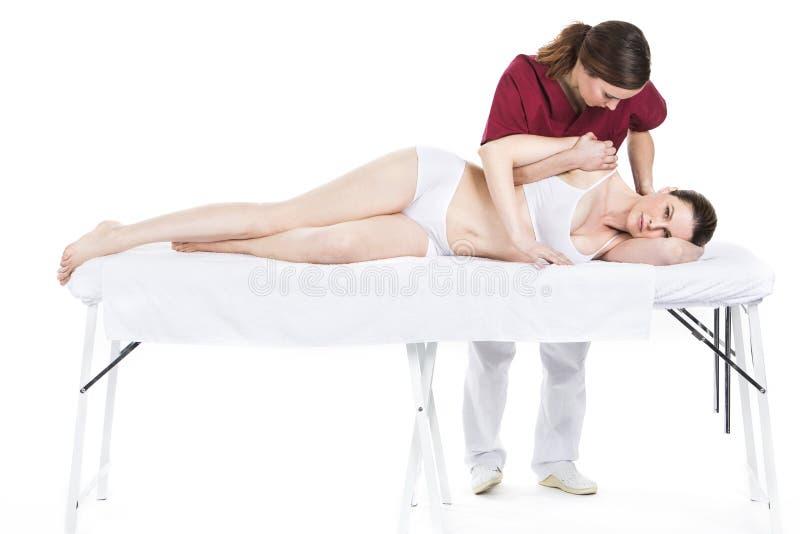 Fysioterapeuten får mobilisering av en skuldra till patienten arkivbild