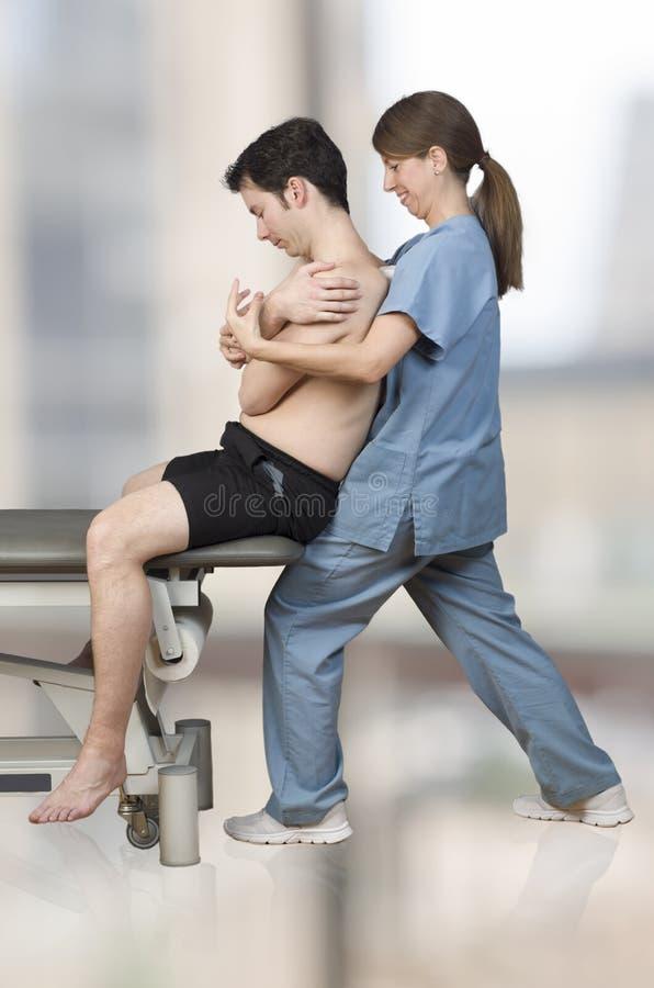 Fysioterapeuten kiropraktor gör en global rygg- behandlig för en manlig patient arkivfoto