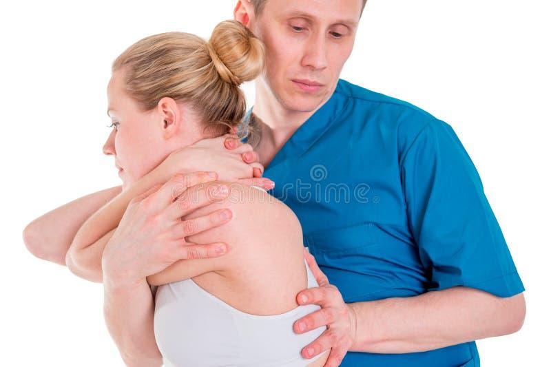 Fysioterapeuten som gör läka behandling mans på, tillbaka Terapeut som b?r den bl?a likformign osteopathy Chiropracticjustering royaltyfria foton