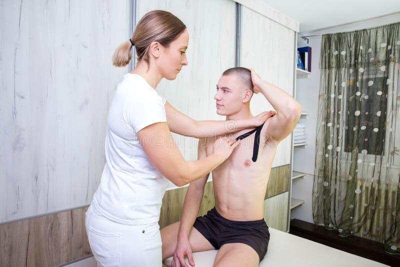 Fysioterapeuten som sätter kinesiobandet på patienter, knuffar och ch fotografering för bildbyråer
