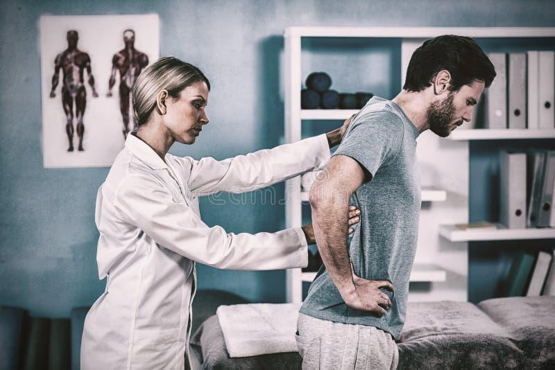 Fysioterapeuten som undersöker, mans tillbaka royaltyfria foton