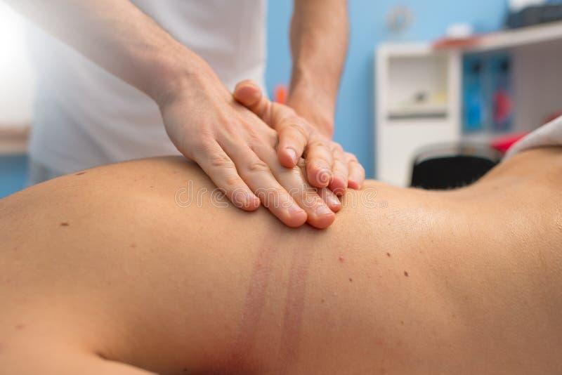 Fysioterapeuten utför en tillbaka massage fotografering för bildbyråer