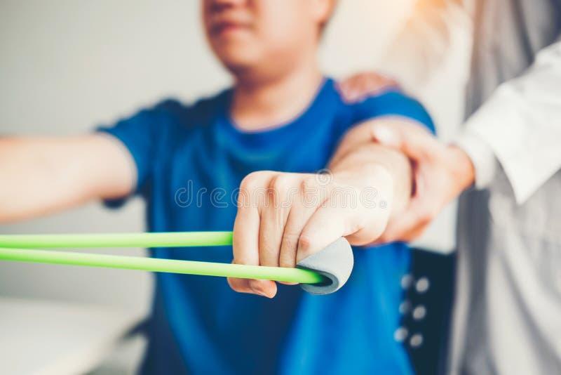 Fysioterapeutman som ger behandling för motståndsmusikbandövning om armen och skuldra av manlig tålmodig sjukgymnastik för idrott arkivbild