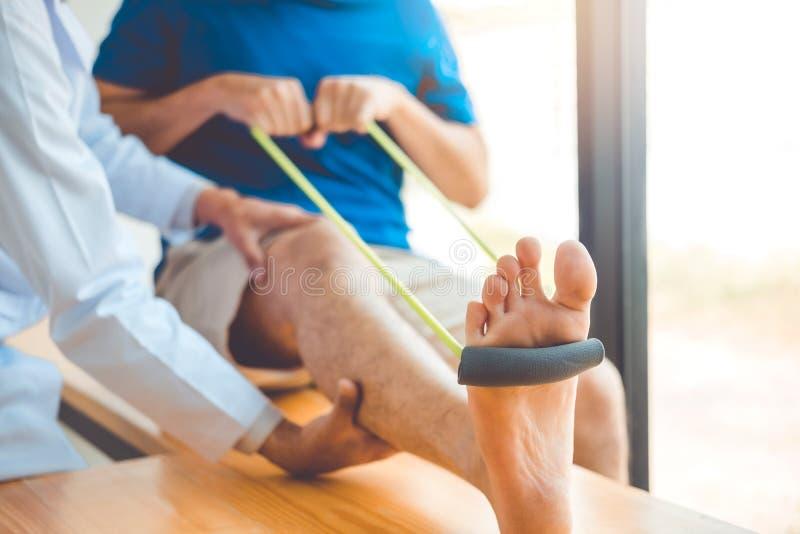 Fysioterapeutman som ger behandling för motståndsmusikbandövning om knä av det manliga tålmodiga sjukgymnastikbegreppet för idrot arkivfoto