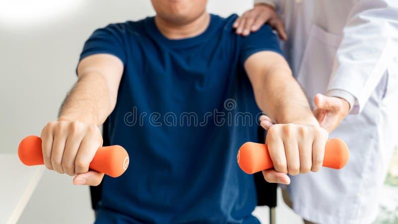 Fysiotherapeut artsenrehabilitatie het raadplegen fysiotherapie die uitoefenend beenbehandeling met pati?nt in fysiokliniek of ho stock foto