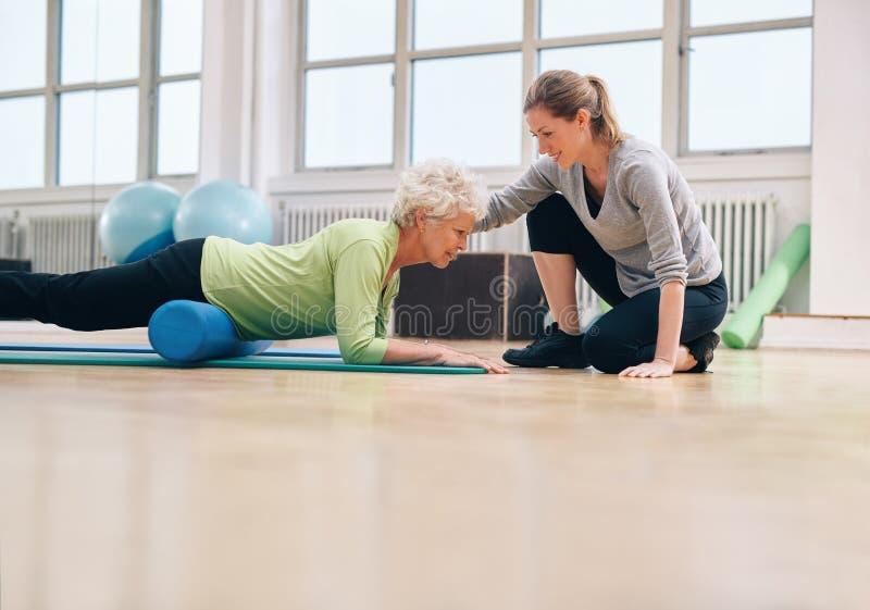 Fysiotherapeut die bejaarde in haar training helpen stock afbeelding