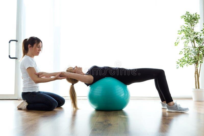 Fysiotherapeut die patiënt helpen om oefening op geschiktheidsbal in fysioruimte te doen royalty-vrije stock afbeelding