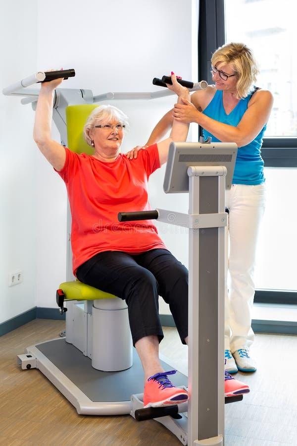 Fysiotherapeut die patiënt met oefeningen helpen stock afbeeldingen