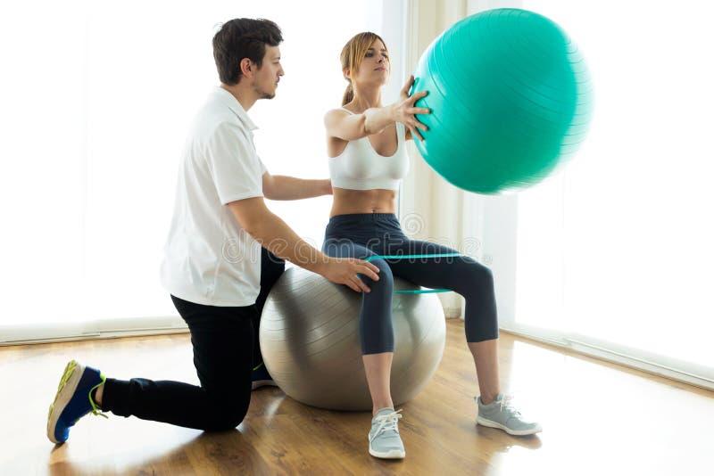 Fysiotherapeut die pati?nt helpen om oefening op geschiktheidsbal in fysioruimte te doen stock foto