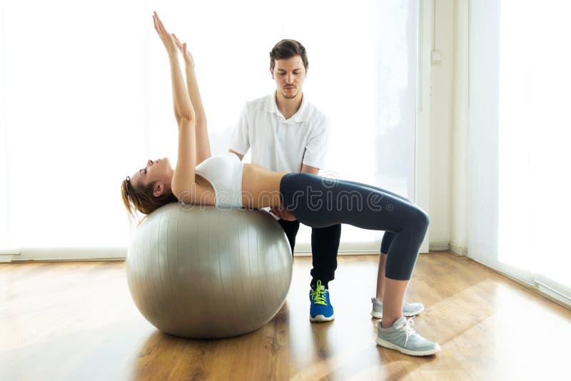 Fysiotherapeut die pati?nt helpen om oefening op geschiktheidsbal in fysioruimte te doen royalty-vrije stock afbeelding