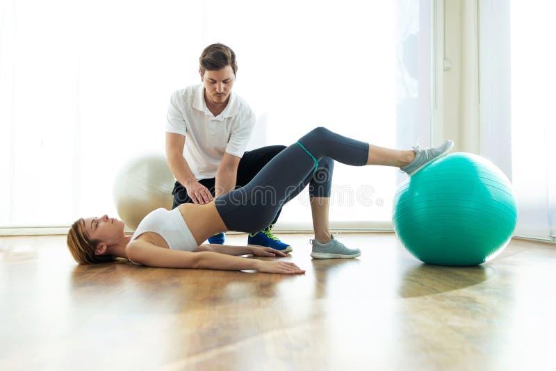Fysiotherapeut die pati?nt helpen om oefening op geschiktheidsbal in fysioruimte te doen royalty-vrije stock afbeeldingen