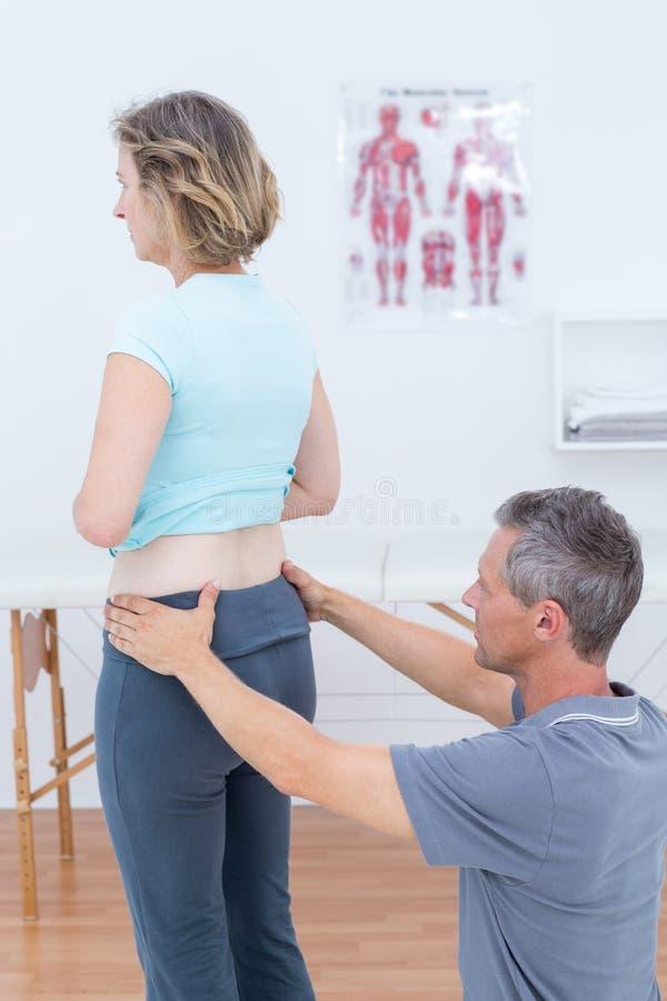 Fysiotherapeut die zijn geduldige rug onderzoeken stock fotografie