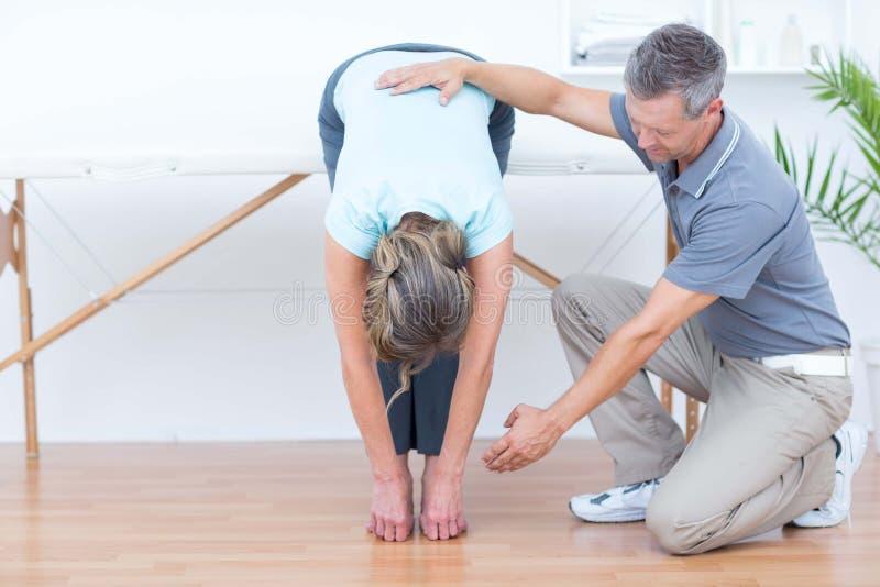 Fysiotherapeut die zijn het geduldige uitrekken bevorderen zich royalty-vrije stock afbeeldingen
