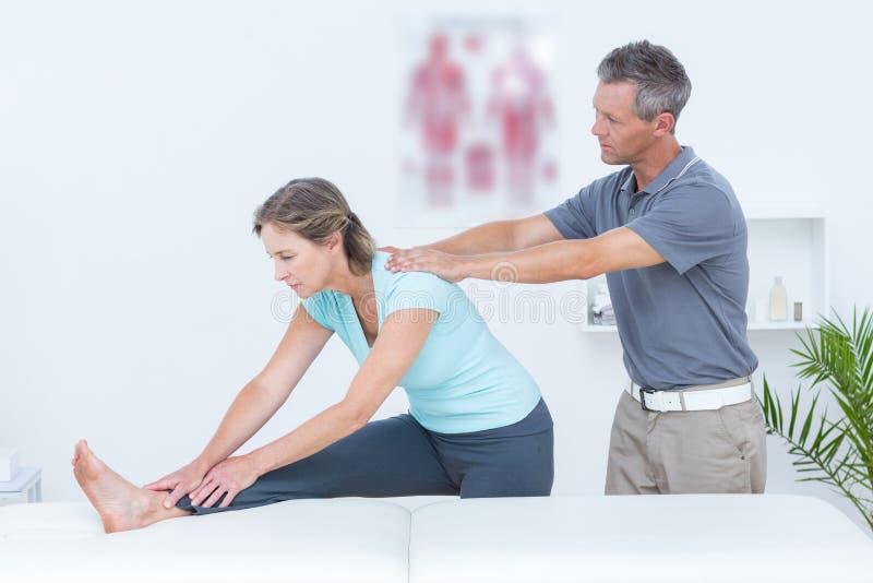 Fysiotherapeut die zijn het geduldige uitrekken bevorderen zich stock afbeeldingen