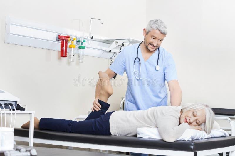 Fysiotherapeut Helping Senior Patient met Beenoefening stock afbeeldingen