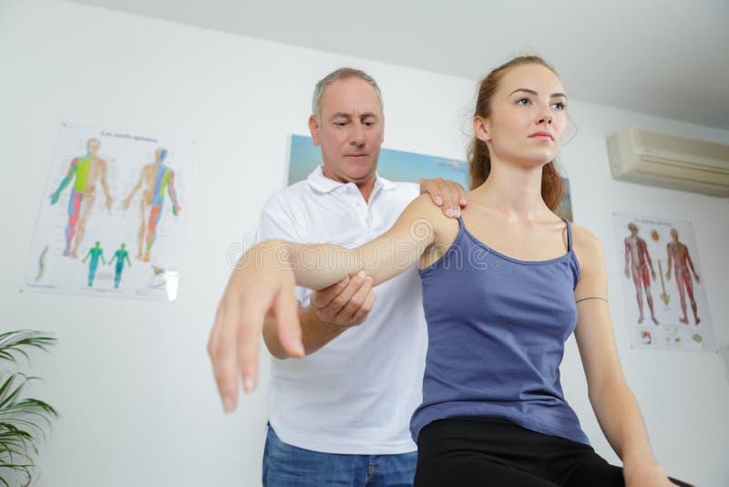 Fysiotherapeut met wapen vrouwelijke patiënt in fysio-ruimte royalty-vrije stock fotografie