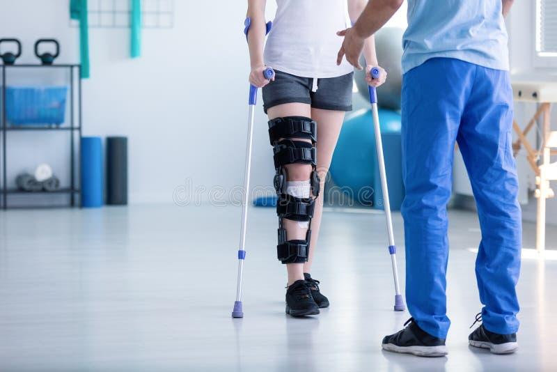 Fysiotherapeut ondersteunende patiënt met orthopedisch probleem stock foto