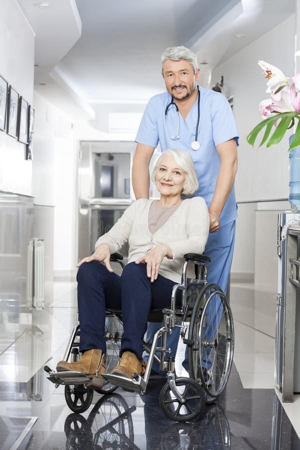Fysiotherapeut Pushing Senior Woman in Rolstoel stock foto's