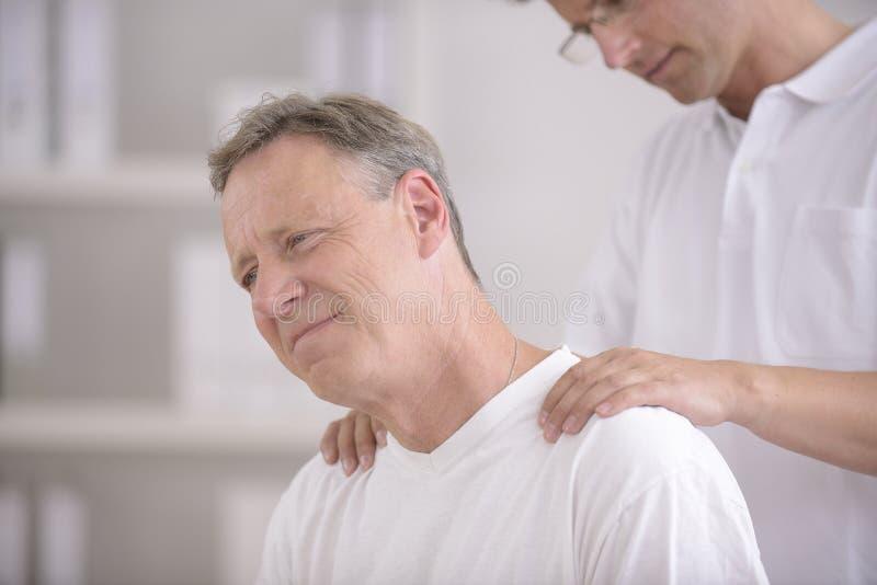 Fysiotherapie: Fysiotherapeut die patiënt masseert stock afbeeldingen