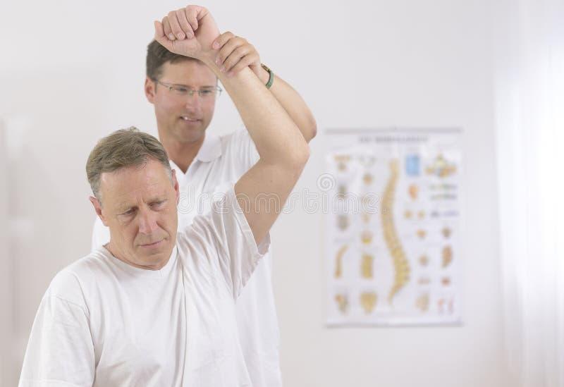 Fysiotherapie: Hogere mens en fysiotherapeut royalty-vrije stock foto