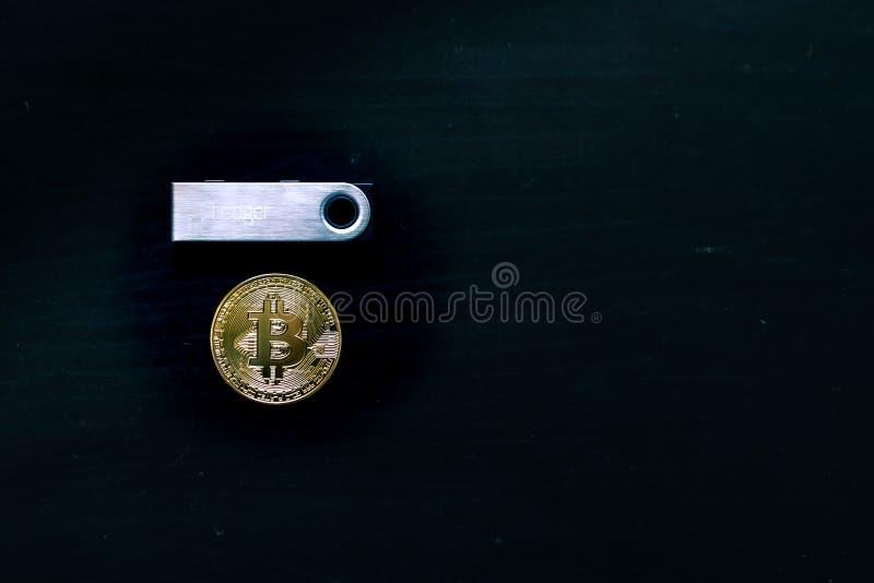 Fysisk bitcoin som sitter under en Nano S s?ker kall pl?nbok f?r huvudbok arkivfoto
