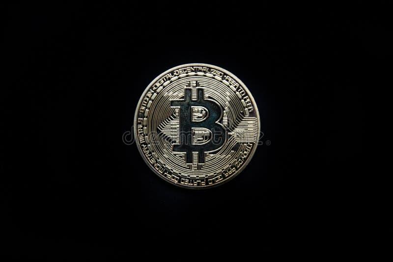 Fysisk guld Bitcoin som isoleras mot en svart bakgrund arkivfoto