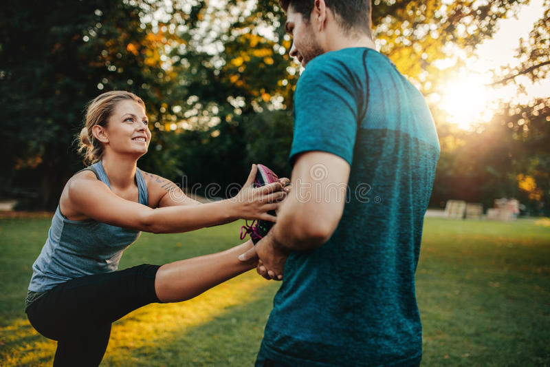 Fysisk instruktör som hjälper kvinnan med benövning royaltyfri bild