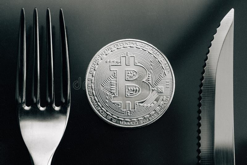 Fysisk silverCrytocurrency mynt mellan gaffeln och knive arkivfoton