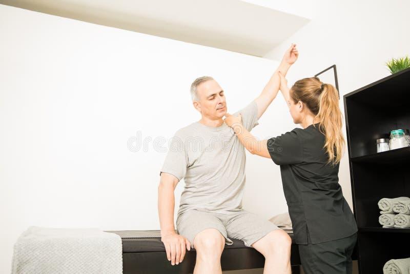 Fysisk terapeut Lifting Injured Hand av patienten i sjukhus royaltyfri bild