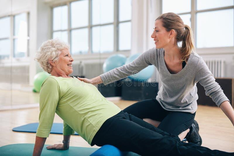 Fysisk terapeut som arbetar med en hög kvinna på rehab royaltyfria bilder
