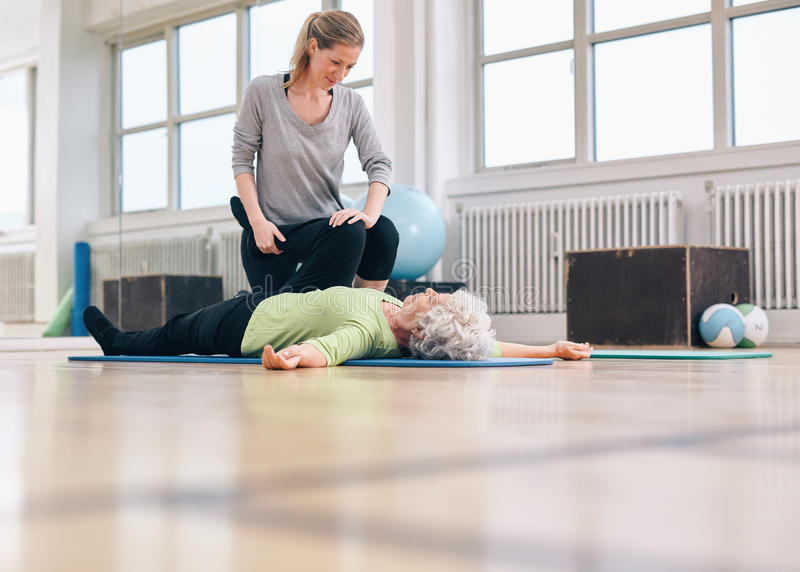 Fysisk terapeut som hjälper den höga kvinnan med benövning royaltyfri foto